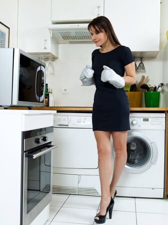 microwave oven: beautiful caucasian woman in a kitchen waiting with anxiety in front of the oven