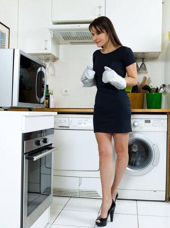 microondas: hermosa mujer cauc�sica en una cocina espera con ansiedad de horno