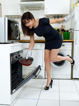 microondas: hermosa mujer cauc�sica en una cocina cocinar pastel de chocolate de la forma de un coraz�n