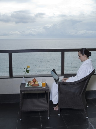 balcony design: beautiful calm and serene woman in palace hotel room at the balcony facing the sea with a computer laptot