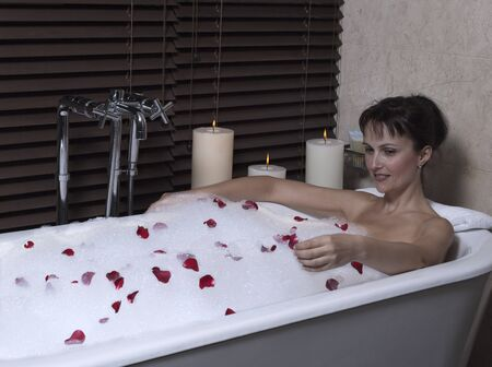 beautiful calm and serene woman in palace hotel room in a bathtub with rose petals and foa Stock Photo - 9841269