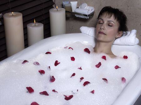 beautiful calm and serene woman in palace hotel room in a bathtub with rose petals and foa Stock Photo - 9823756