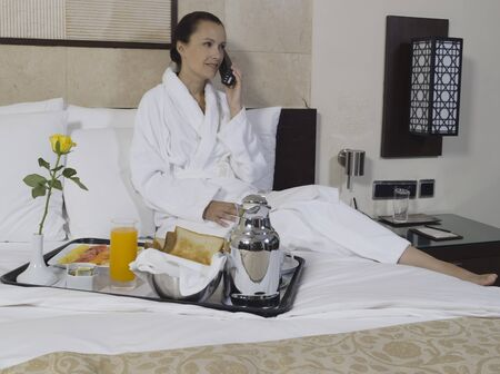 beautiful calm and serene woman in palace hotel room having her breakfast phoning Stock Photo - 9823755