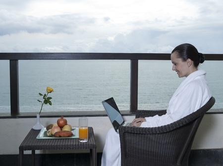 bathrobes: hermosa mujer tranquila y Serena en la habitaci�n del hotel palace en el balc�n frente al mar con una laptot de equipo