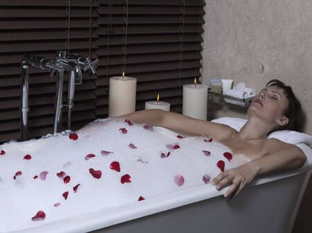 beautiful calm and serene woman in palace hotel room in a bathtub with rose petals and foa Stock Photo - 9841267
