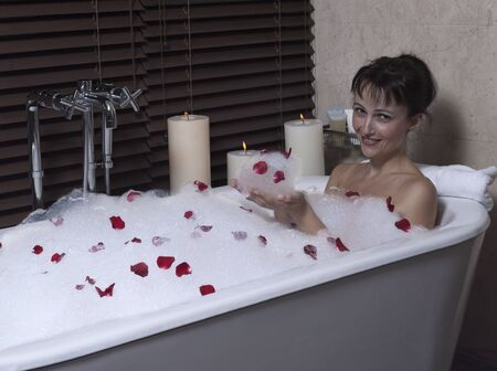 beautiful calm and serene woman in palace hotel room in a bathtub with rose petals and foa Stock Photo - 9841285