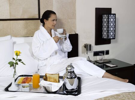 continental: beautiful calm and serene woman in palace hotel room having her breafas LANG_EVOIMAGES
