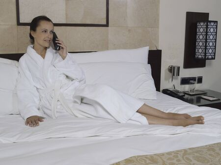 beautiful calm and serene woman in palace hotel room lying on a king size bed phonig Stock Photo - 9823734