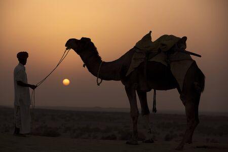 man looking at his camel during sunset khuri dunes in thar desert near jaisalmer in rajasthan state in indi Stock Photo - 9800092
