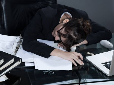 sleepiness: beautiful brunette business woman at her desk sleeping LANG_EVOIMAGES