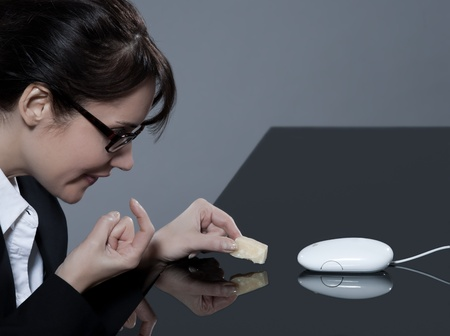 ridicolo: donna bella bruna business alla sua scrivania cercando di intercettare il suo mouse del computer con formaggio LANG_EVOIMAGES