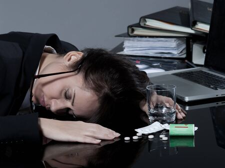 overdose: beautiful brunette business woman at her desk committes suicide