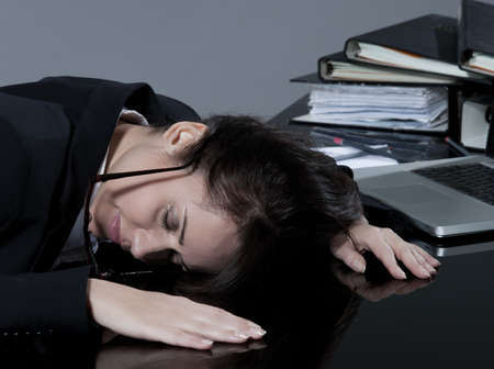 beautiful brunette business woman at her desk sleeping Stock Photo - 9823751