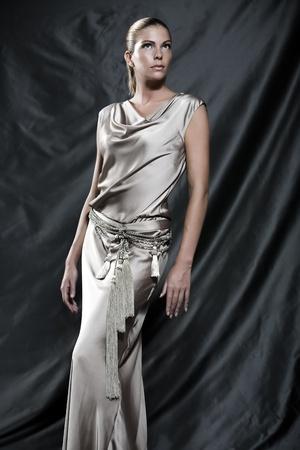 toga: Immagini di moda di una bella donna che indossa abito da cocktail in raso crema LANG_EVOIMAGES