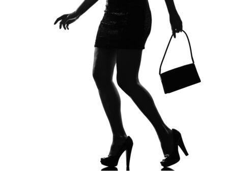 feminity: stylish sexy silhouette caucasian beautiful woman legs close=up details walking on studio isolated white background LANG_EVOIMAGES