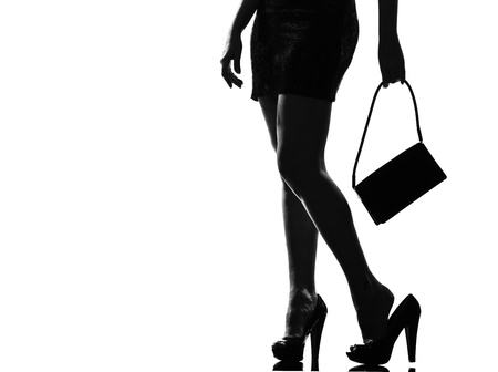 feminity: stylish sexy silhouette caucasian beautiful woman tired painful feet legs close up details standing waiting on studio isolated white background
