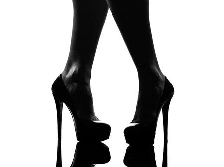 backlit: stijlvol silhouet blanke mooie vrouw benen schoenen hoge hakken stileletto silhouet op studio witte achtergrond