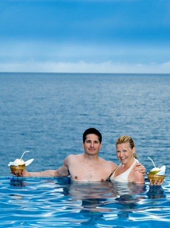 beautiful caucasian couple enjoying their vacation in a beautiful swimming pool by the seasid Stock Photo - 9823749