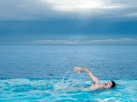 man swimming in a beautiful swimming pool by the seasid