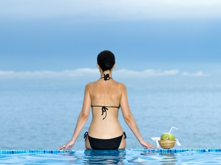 woman siiting on a the edge of a swimming pool looking at the se Stock Photo - 9823643