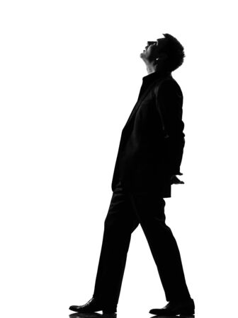 interested: silhouette caucasian business man  walking musing looking up expressing behavior full length on studio isolated white background