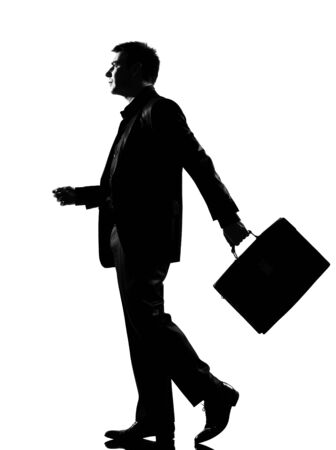 people walking white background: silhouette caucasian business man   walking profile with briefcase  full length on studio isolated white background
