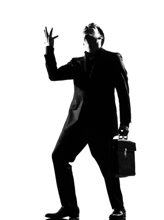 displeased businessman: silhouette caucasian business man  expressing anger adversity despair looking up behavior full length on studio isolated white background