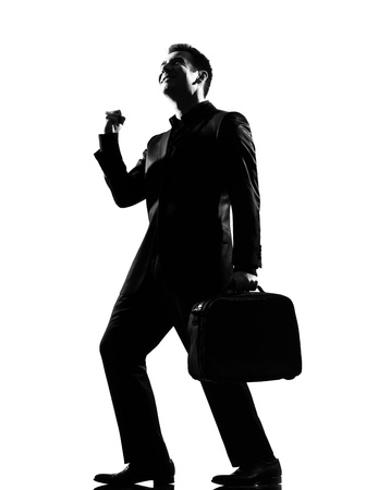 clenching fists: silhouette caucasian business man  expressing happy joy winning behavior full length on studio isolated white background