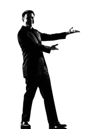 introduce: silhouette caucasian business man  expressing  showing gesture introducing presentationsimiling  behavior full length on studio isolated white background LANG_EVOIMAGES