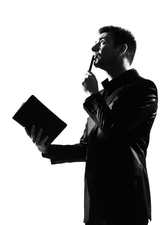 the reader: silhouette caucasian business man with note pad thinking expressing behavior full length on studio isolated white background LANG_EVOIMAGES