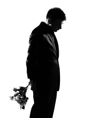 adult dating: silhouette caucasian business man offering flowers expressing behavior full length on studio isolated white background LANG_EVOIMAGES