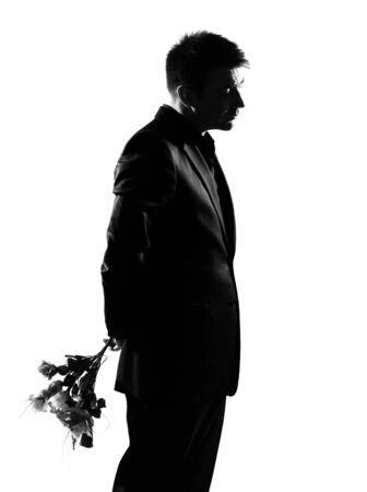 desilusion: hombre de negocios cauc�sico de silueta ofreciendo flores expresando la longitud total de comportamiento en estudio aislado fondo blanco