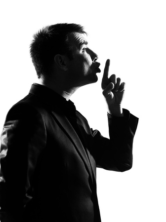 quiet adult: silhouette caucasian business man  hushing silence profile finger on lips full length on studio isolated white background LANG_EVOIMAGES