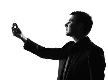 silhouette caucasian business man  holding light bulb expressing behavior full length on studio isolated white background Stock Photo - 9800053