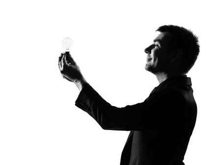 silhouette caucasian business man  holding light bulb expressing behavior full length on studio isolated white background Stock Photo - 9799960