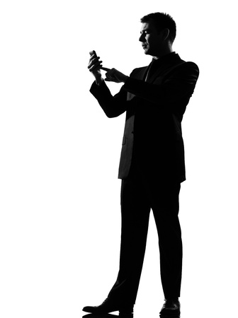 silhouette caucasian business man on the phone  sms text messaging full length on studio isolated white background Stock Photo - 9799876