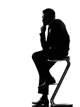 focused: silhouette caucasian business man thinking pensive sititting on foot stool full length on studio isolated white background