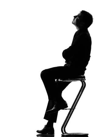 silhouette caucasian business man thinking pensive sititting on foot stool full length on studio isolated white background Stock Photo - 9799950
