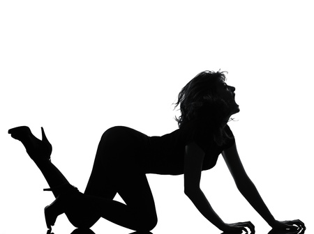 crouching: full length silhouette in shadow of a young woman crouching  roar in studio on white background isolated LANG_EVOIMAGES