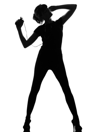 earphone: full length silhouette in shadow of a young woman ancing and listening music on mp3 audio player  in studio on white background isolated LANG_EVOIMAGES