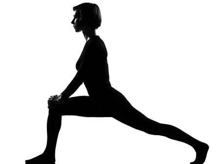 stretch out: woman exercising fitness yoga stretching in shadow grayscale silhouette full length in studio isolated white background