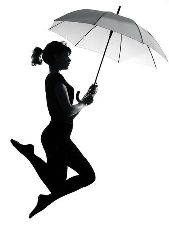 donna volante: sagoma a figura intera in ombra di una giovane donna volante con ombrello aperto in studio su sfondo bianco isolato LANG_EVOIMAGES