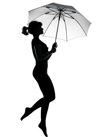 impulse: full length silhouette in shadow of a young woman flying with open umbrella  in studio on white background isolated