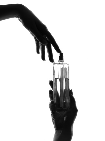detail close-up silhouette in shadow of a  woman hands holding perfume in studio on white background isolated Stock Photo - 9800015