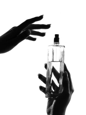 detail close-up silhouette in shadow of a  woman hands holding perfume in studio on white background isolated Stock Photo - 9800077