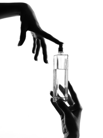 scent: detail close-up silhouette in shadow of a  woman hands holding perfume in studio on white background isolated