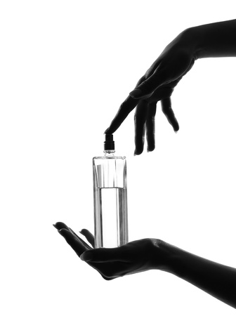 perfume bottle: detail close-up silhouette in shadow of a  woman hands holding perfume in studio on white background isolated