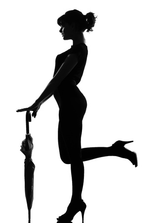 full length silhouette in shadow of a young woman with closed umbrella  in studio on white background isolated Stock Photo - 9799849