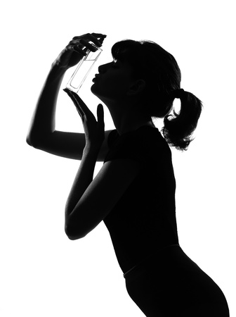 silhouette in shadow of a young woman kissing her perfume bottle  in studio on white background isolated Stock Photo - 9800062