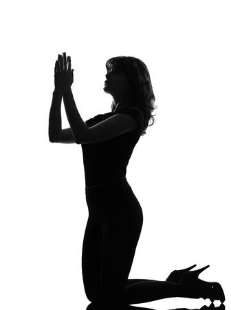 voller Länge Silhouette im Schatten einer jungen Frau Knien beten flehe im Studio auf weißem hintergrund isoliert